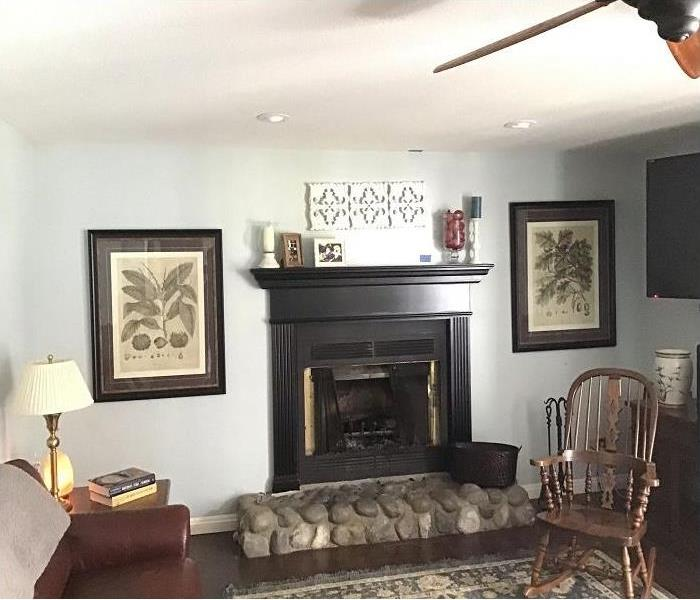 living room with white walls, fire place with mantle pictures on walls