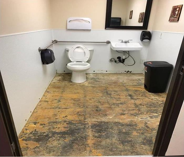 public bathroom with floor pulled during demo for drying